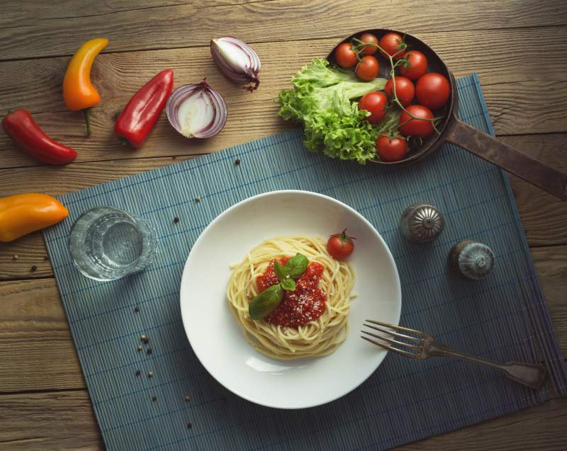 Spaghetti in a bowl with fresh produce.